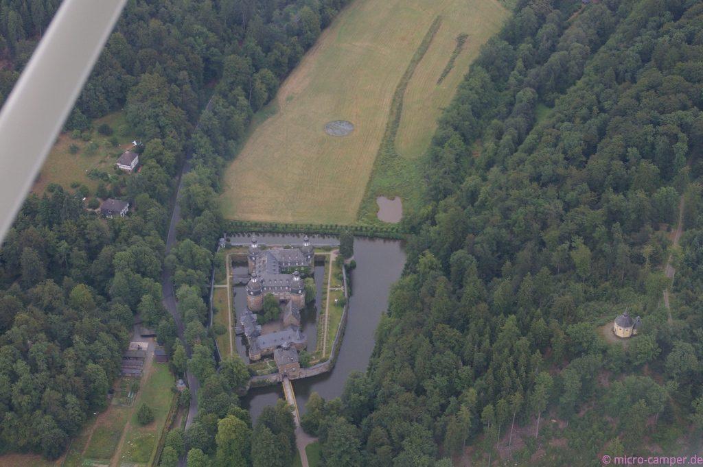 das Wasserschloss Crottorf und die Kapelle (rechts) aus der Luft