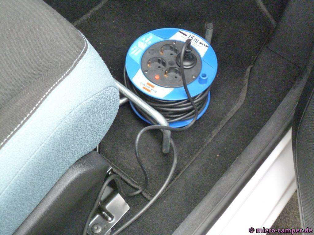 Kabeltrommel im Beifahrerfußraum, eingesteckt das Kabel vom Ladegerät