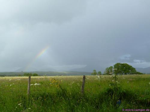 Im Dunst hinter dem Regenbogen zeichnet sich die Vulkankette ab