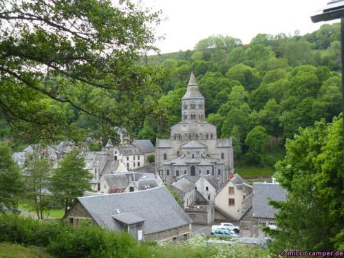 Durch das frische Grün des Hügels wirkt das Grau des Dorfes fast freundlich