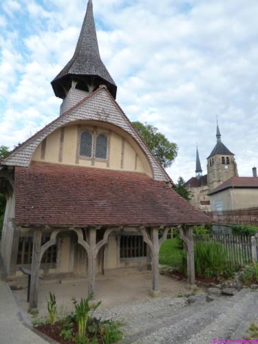 Die alte Holzkapelle und dahinter die große Kirche aus Stein