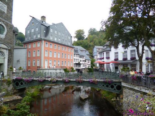 Das Rote Haus in Monschau an der Rur, am Ende der Brücke die ev. Stadtkirche