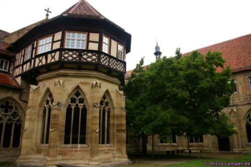 Das Brunnenhaus von außen, daneben eine große Magnolie