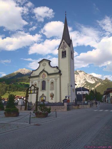 St. Vigils Kirche ist umrahmt von Dolomitgipfeln